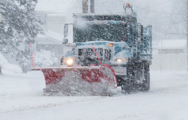Snow plow clearing the road during a blizzard